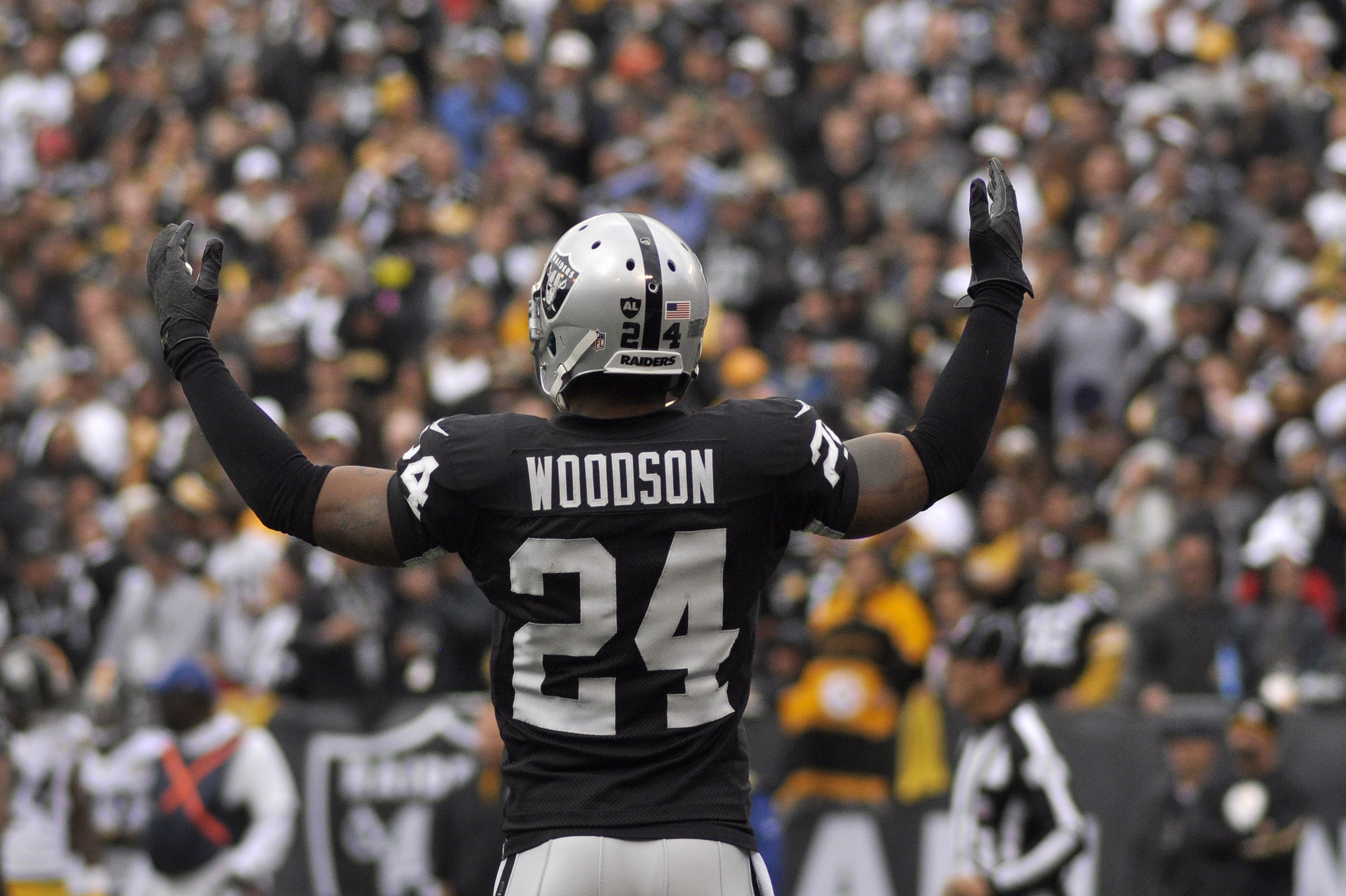 Oakland Raiders cornerback Charles Woodson (24) pumps up the crowd during the football game against the Pittsburgh Steelers at O.co Coliseum in Oakland, Calif., on Sunday, Oct. 27, 2013. The Raiders won 21-18.